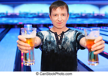 Happy young man holds two big glasses of beer in bowling...