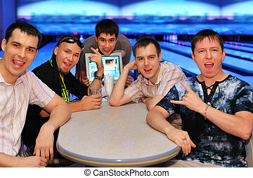 Five happy friends sit at table and grimace in bowling;...