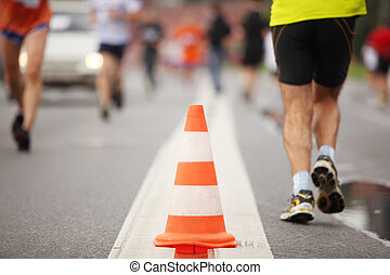 Big color cone on road between running people, close-up view