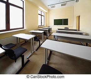 Empty beige classroom with wooden school desks and simple...