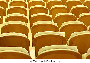 Rows of yellow comfortable beige chairs with wooden back, view from back