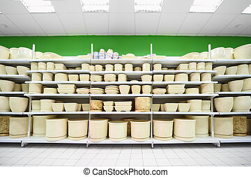 Shelves with variety of beige and colorful clay flowerpot...