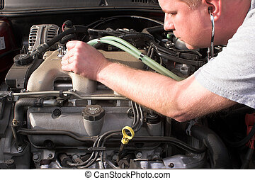 Auto Mechanic - An auto mechanic diagnosing a problem on an...