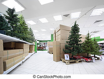 Shelves with variety of artificial Christmas tree inside large supermarket