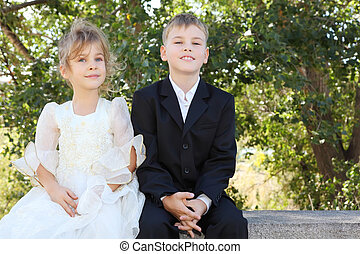 happy little brother wearing black suit and sister wearing beautiful white dress sit and smile; focus on boy