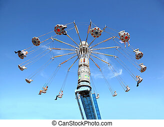 Happy people on swinging circular chained carousel at high blue sky
