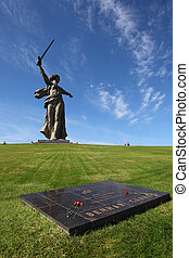 Monument Motherland in Volgograd, Russia; commemorative plate with flowers; people near memorial