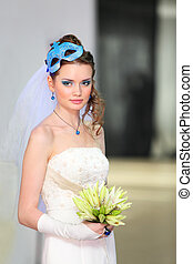 beautiful young bride wearing in white dress with blue makeup and mask in hairdo