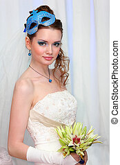 beautiful young bride wearing in white dress with blue makeup and mask in hairdo looks at camera