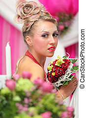 beautiful young bride with bouquet of red roses and unusual makeup