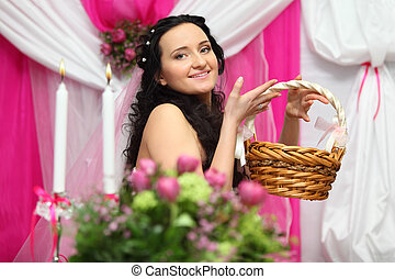 beautiful young bride holds wicker basket and looks at...