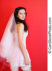 beautiful young bride wearing in white short dress on red background