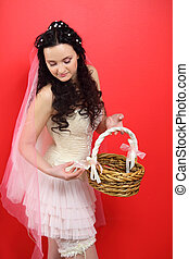 beautiful young bride wearing in white short dress holds wicker basket and looks down on red background