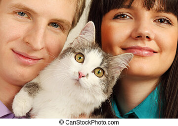 Smiling young husband and wife hold surprised cat; focus on...