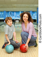 beautiful young mother and son keep red and blue balls ant...