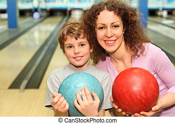 beautiful young mother and son keep red and blue balls in...