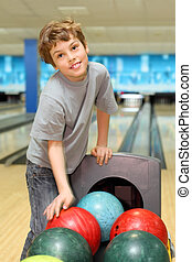 smiling happy boy stands near many colorful balls in bowling...