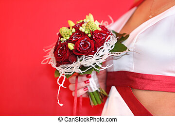 hand of beautiful bride wearing in white dress with red ribbons holds bouquet of roses on red background