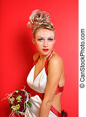 beautiful young bride wearing in original dress witn bouquet of roses on red background
