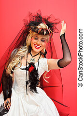 laughing bride wearing black net gloves and unusual hat with veil on red background