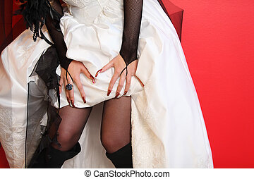 hands of bride and hem of unusual white wedding dress on red...