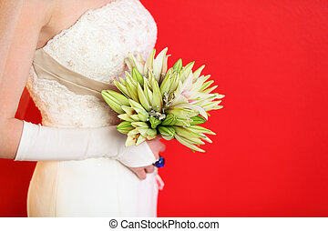 hands of young bride hold bouquet of lilies on red...