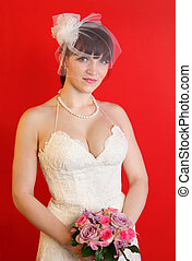 bride wearing white dress holds bouquet of roses on red background
