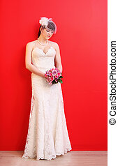 beautiful bride wearing long white dress holds bouquet of roses on red background