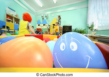 multicolored balls lie in large container; kids play witn adults in kindergarten
