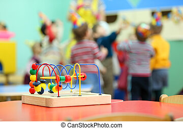 Colorful wooden toy stand at red table in kindergarten;...
