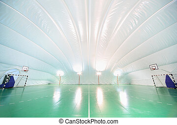 Empty indoor sports ground, plastic white ceiling and walls,...