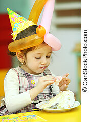 little girl dressed in yellow hat eating cake on her...