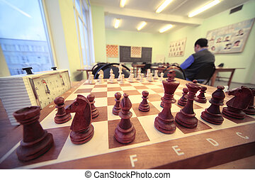 Chess stand on chessboard in room of chess club; brown wooden figures