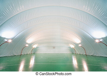 People train in indoor sports ground, plastic white ceiling...