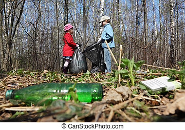 Brother and sister with black bags collect trash in park at...