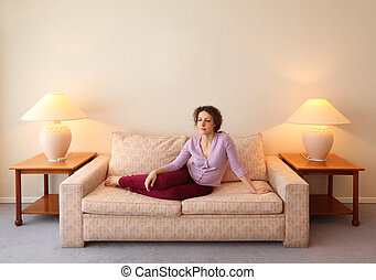 Beautiful young woman lies on couch in simple comfortable...