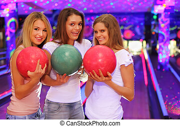 three smiling girls with balls stand in bowling club and...