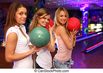 three happy girls with balls stand in bowling club and prepare to throw; focus on girl in middle