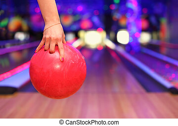 Female hand with red nail polish holding ball before throwing in bowling club