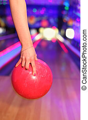Female hand with red nail polish holding red ball before throwing in bowling club