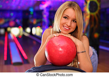 happy beautiful girl stands and bases on red ball in bowling...