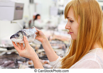Blonde girl wearing white shirt holds fish in store; shallow...