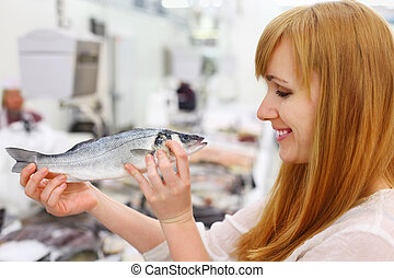 Smiling girl wearing white shirt holds fish in store;...
