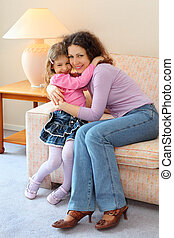 Smiling mother and daughter sit on couch and hug in cozy room