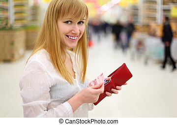 Happy girl gets money from her red purse in store and looks at camera; shallow depth of field