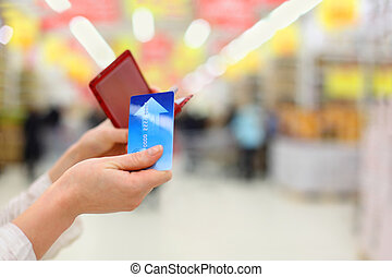 Woman gets credit card from purse in store; shallow depth of...