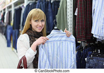 Happy girl wearing scarf holds male shirt in shop; shallow depth of field