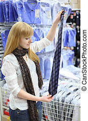 Girl wearing scarf holds packed tie in shop; shallow depth of field