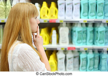Blonde girl chooses abstergent in shop; shallow depth of field