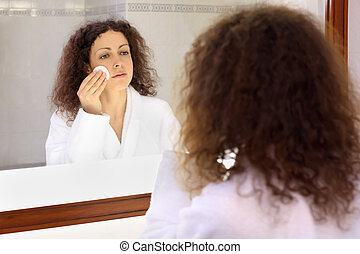 Smiling woman dressed in white bathrobe stands near mirror and removes make-up
